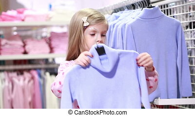 Baby girl looking at clothes in fashionable shop