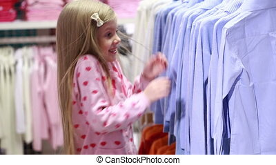 Baby girl looking at clothes in fashionable shop. pretty...