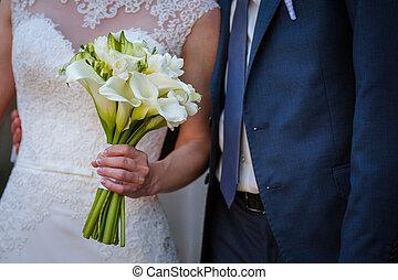 Wedding pastel bouquet closeup in front of couple - groom...