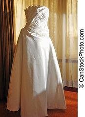 Wedding Gown - White wedding gown by a large glass window...
