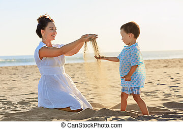 Mother with child play with sand on sea beach - Happy family...