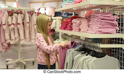 Baby girl looking at clothes in fashionable shop pretty...