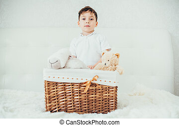 boy hid behind a basket with soft toys playing