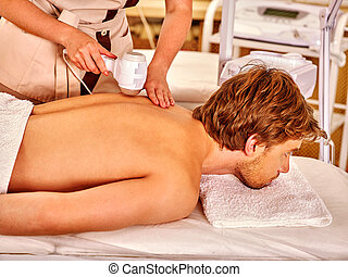 Young man receiving electric facial massage - Strong man...