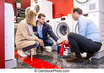 Salesman Explaining Product To Customers In Washing Machine Department