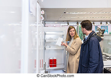 Young Couple Buying Refrigerator In Hypermarket - Young...