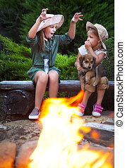 Two sisters talking stories by the campfire