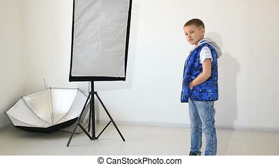 Photographer taking pictures of the child in the studio boy...