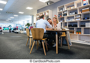 Salesman Assisting Couple In Electronics Shop
