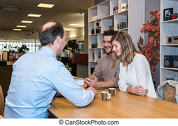 Salesman Interacting With Couple In Electronics Shop