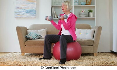Senior lady exercising at home - Senior woman using...