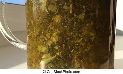 Slow movement of leaves of tea in a glass teapot.