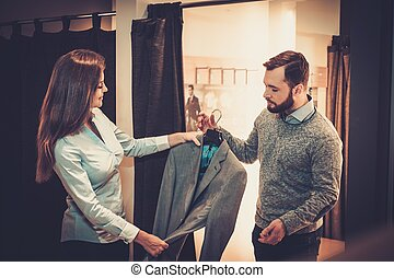 Confident handsome man with beard choosing a jacket in a...