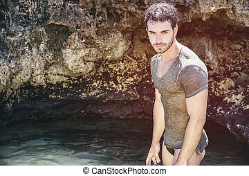 Athletic man in the sea or ocean by rocks, wet t-shirt -...