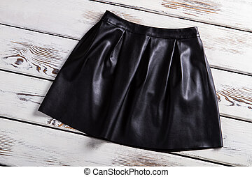 Black leather skirt with folds. Leather skirt on wooden...