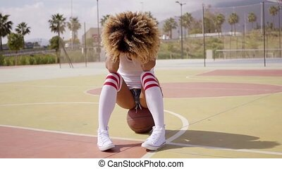 Attractive young woman sitting on a basketball - Attractive...