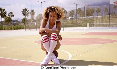 Pretty young female athlete sits on basketball - Pretty...