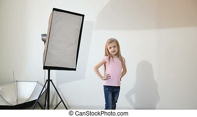 Photographer taking pictures of the child in the studio girl...