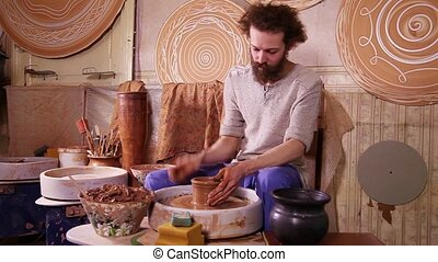 Potter making clay jug - Potter working with clay on a...