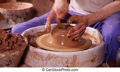 Hands of a potter close-up - Hands of a potter creating an...