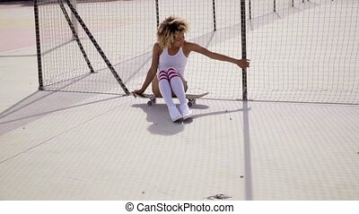 Young skater relaxes beside tennis court - Young black...