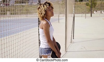 Young woman with skateboard leans against fence - Pretty...
