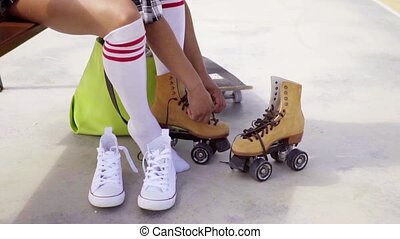 Young woman sits on bench to tie her skates - Young woman...