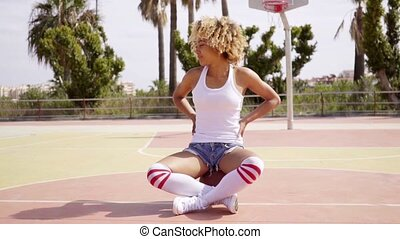 Blond young woman sits cross legged on ball