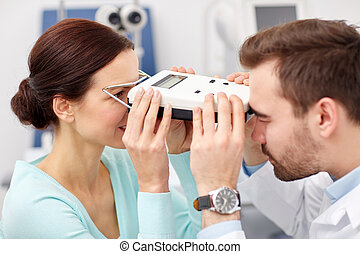 optician with pupilometer and patient at eye clinic - health...