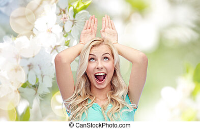 happy smiling young woman making bunny ears