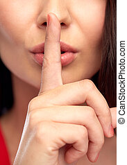 close up of woman face holding finger on her lips - people,...