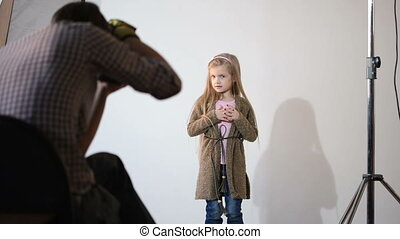 Photographer taking pictures of the child in the studio....