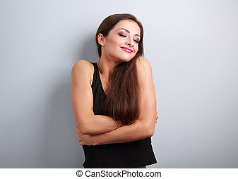 Happy sporty fit woman hugging herself with natural...