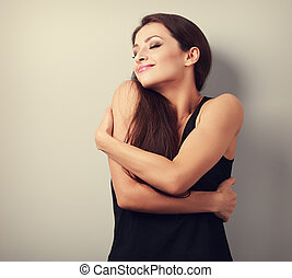Happy strong sporty woman hugging herself with natural...