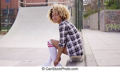 Young woman sitting on her skateboard at the rink - Pretty...