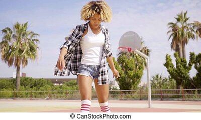 Woman in roller skates on basketball court - Young single...
