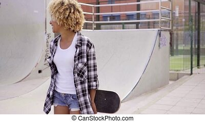 Charismatic young woman holding a skateboard - Charismatic...