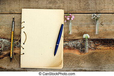 handmade sketchbook with old pen and small bouquet of...
