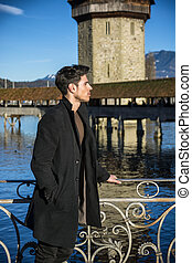 Man standing near metal fence in Lausanne - Handsome man...