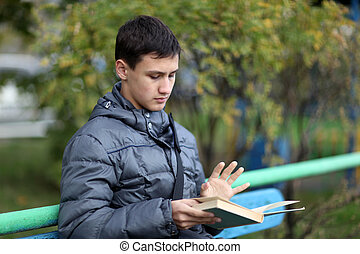 boy outdoors reading book