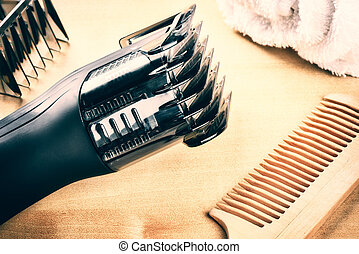 Setting with hair clipper and wooden comb. Closeup shot