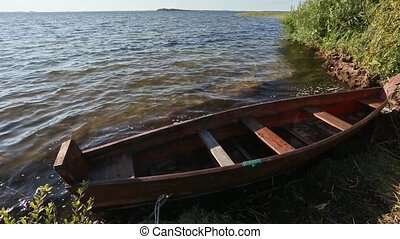 Wooden Boat near Shore - Summer evening lake view with...