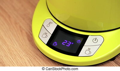 Person starts boil of electric tea - Finger pushing button...