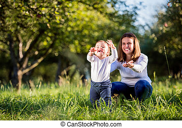 Mother with her son making first steps, green nature