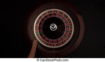 Croupier spins the roulette then stops black - Croupier...