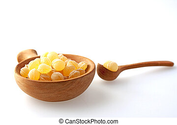 Candies flavour of honey in a wooden bowl with spoon