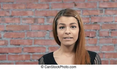 Attractive girl depict admiration in camera. Casting. Brick...