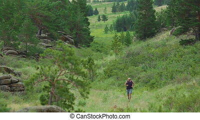 Mountain valley jogging - Middle-aged men jogging on the...