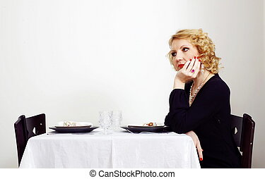 single woman sits besides served table