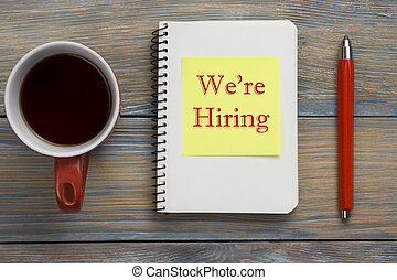 We are Hiring. Office desk table with notepad, pencil and coffe cup. Top view.